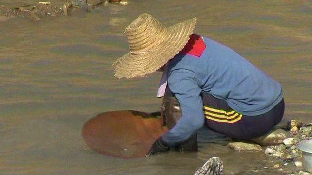 Woman hunts for gold at Thailand's Wang river.