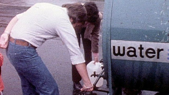 Man fills bucket from water bowser 1976
