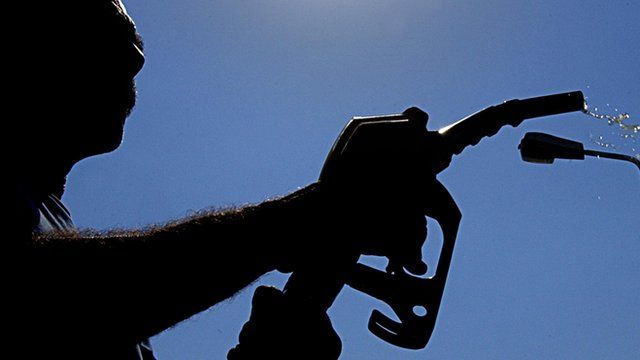 A silhouette of a man holding a fuel pump