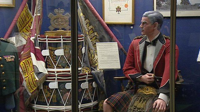 Model of Regimental Highlander sitting down in full dress with regimental drums and flags