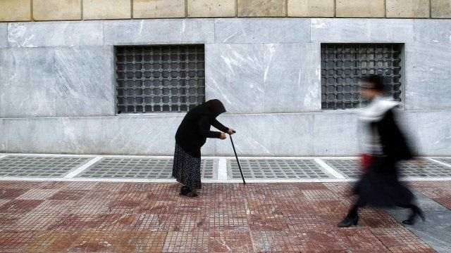 A woman beggar walks by the Bank of Greece in central Athens