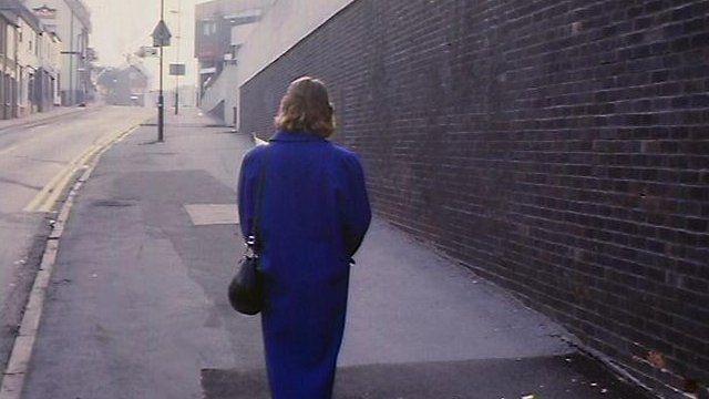 Woman walking down deserted street