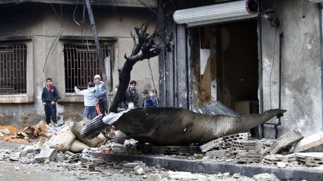 Children next to a damaged building in Homs