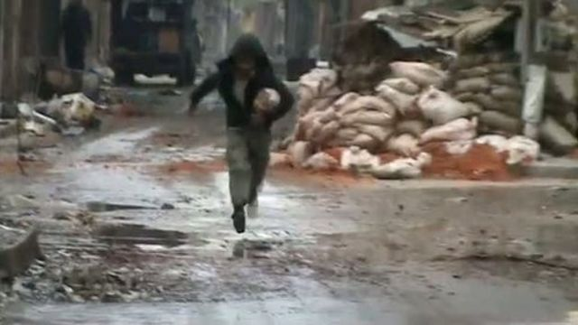 An image grab from a video uploaded on YouTube on March 7, 2012, shows a man running in the Homs neighbourhood of Bab Tadmur