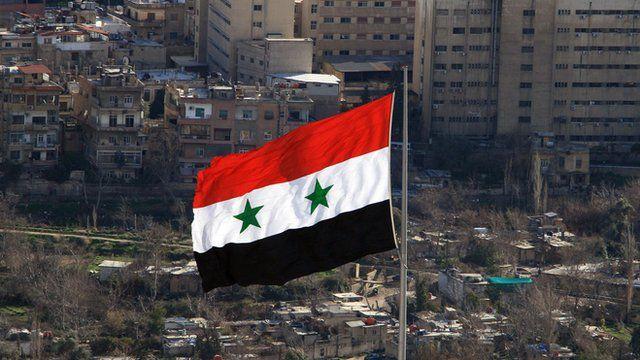 A Syrian flag flies over Damascus