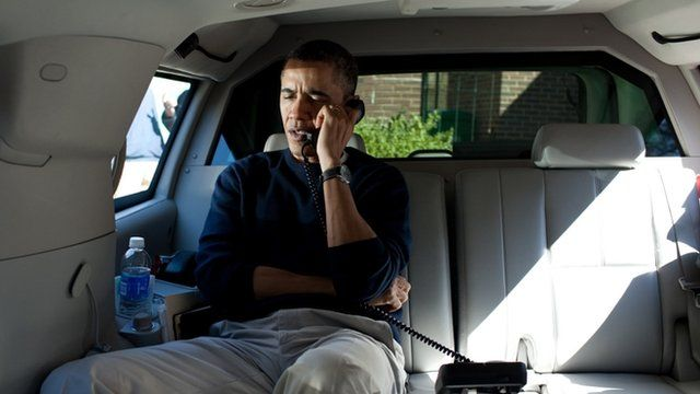 President Barack Obama talks on the telephone with Afghanistan President Hamid Karzai from inside his limousine.