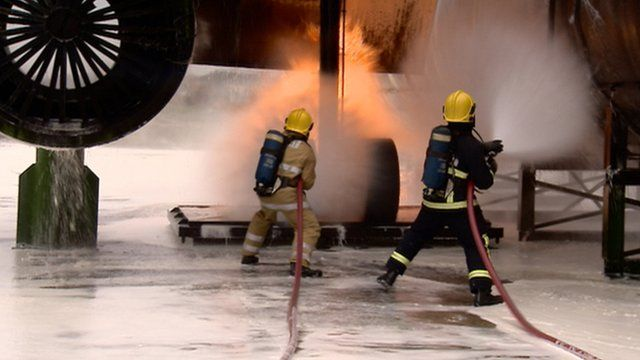 Firefighters put out a fire at the airport training facility