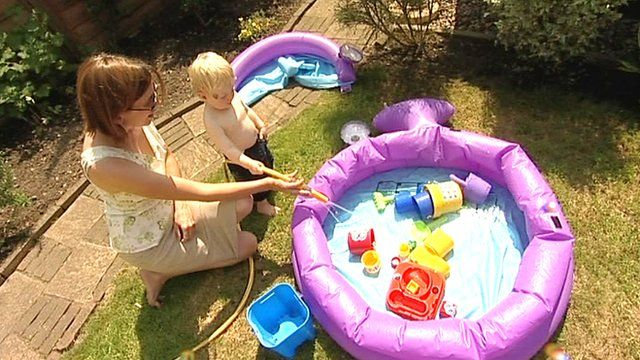 A mother fills up her paddling pool with a hosepipe