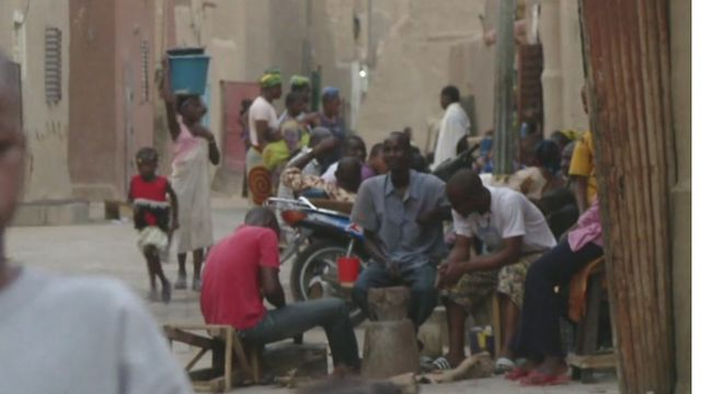 People sitting or going about their daily tasks in Mali.
