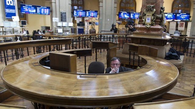 A broker sits in the stock exchange in Madrid