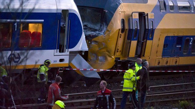 Care providers and policemen walk on the site where two trains collided