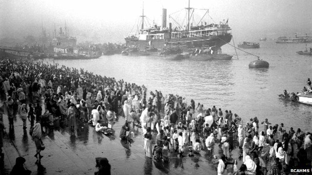 A ship docks in a harbour as people gather by the shore