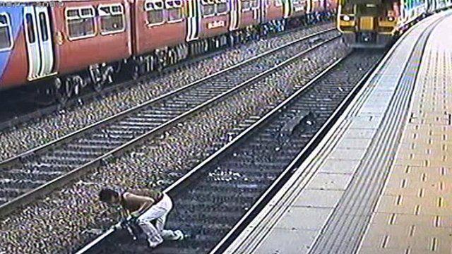 Still of CCTV footage of woman on rail tracks
