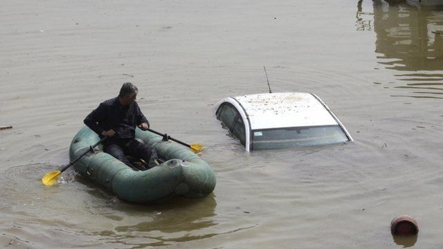 A man rows in a rubber boat at flooded area in the centre of Tbilisi, Georgia