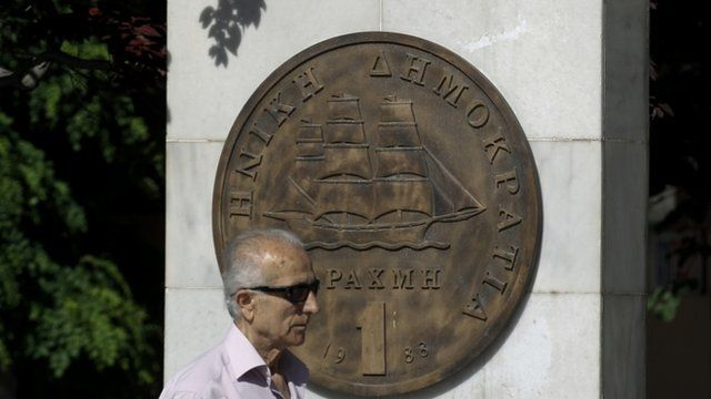 Man makes his way past a replica of a one drachma coin outside the Athens Town Hall