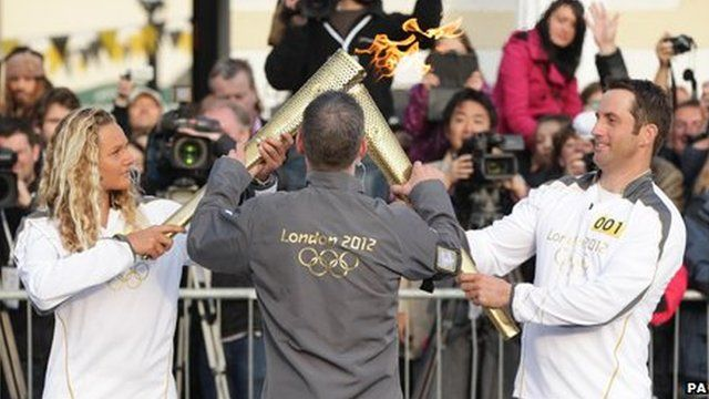 """Ben Ainslie's torch """"kissed"""" that of surfer Tassy Swallow to pass the flame"""