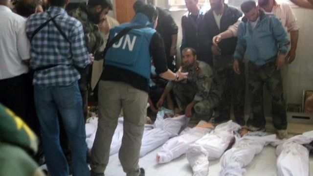 UN observers at a hospital morgue before in the central Syrian town of Houla