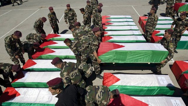 Palestinian security forces carry flag-draped coffins
