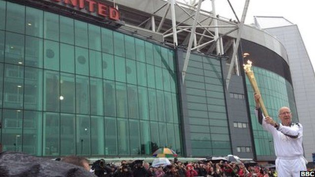 Sir Bobby Charlton outside Old Trafford with the Olympic flame