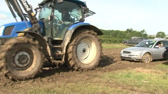 A tractor pulling out a car from the car park after the Isle of Wight Festival