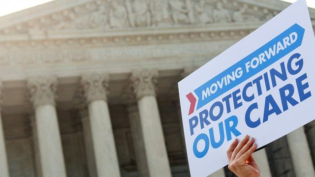 Demonstrators protest as they await a decision by the US Supreme Court on the healthcare act