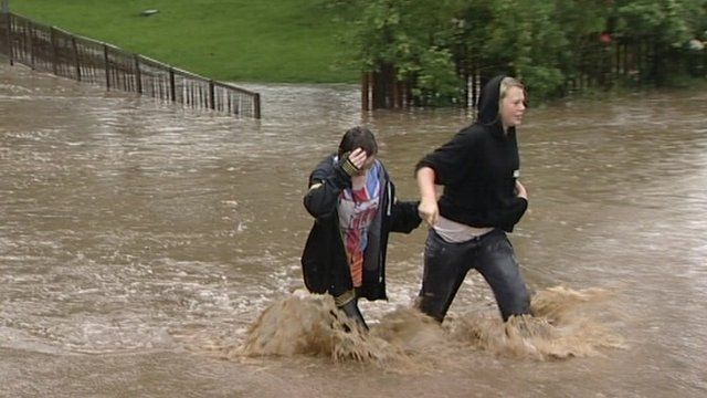 Two people wade through flood water