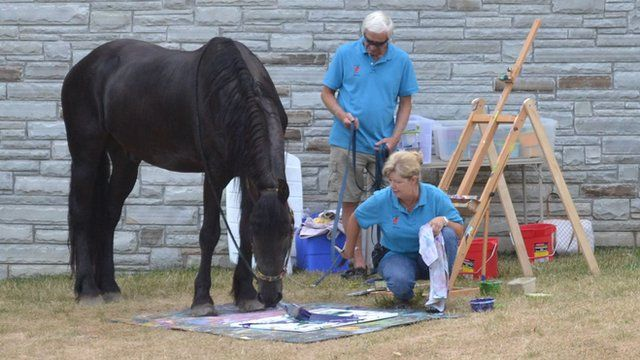 Justin the horse painting with his owner.