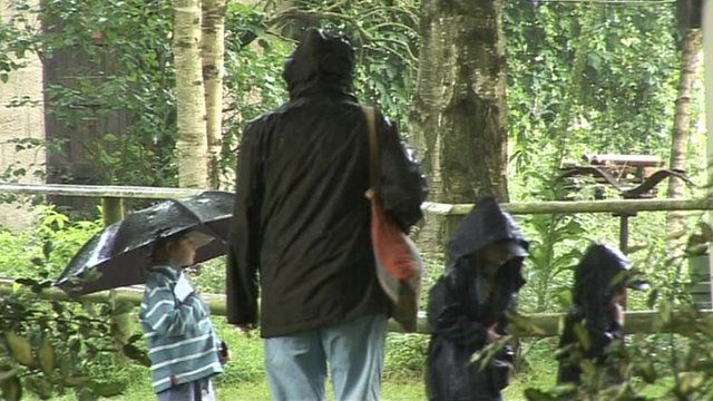 A family wearing raincoats and with an umbrella in the rain