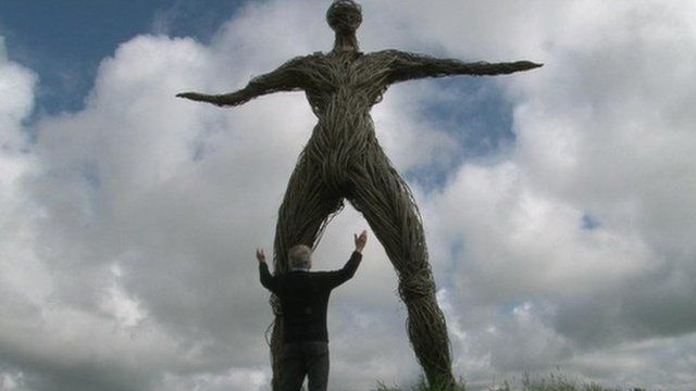 Man standing in front of a Wickerman effigy