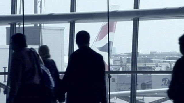 Passengers at an airport walking past the window