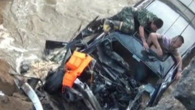 A rescuer helping the driver to safety