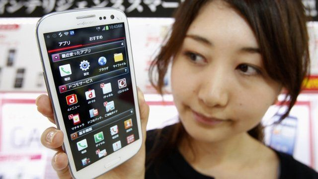 An employee of Japan's largest mobile carrier NTT Docomo Inc holds a Samsung Galaxy S III smartphone
