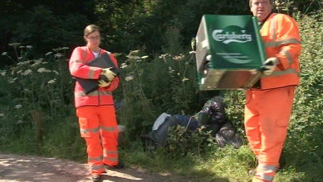 Workers collecting fly-tipped waste