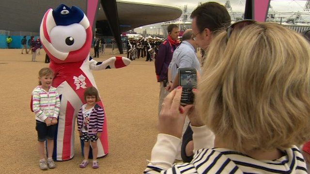 People taking photographs of the Olympic mascot