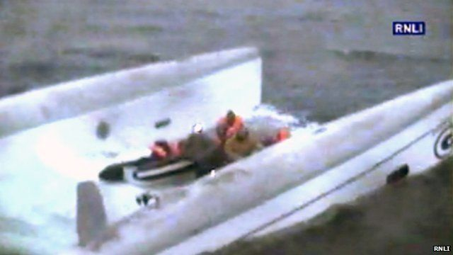 People stranded on an upturned catamaran