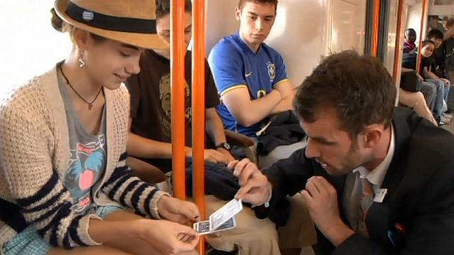 Danny Hall performing a card trick with a passenger