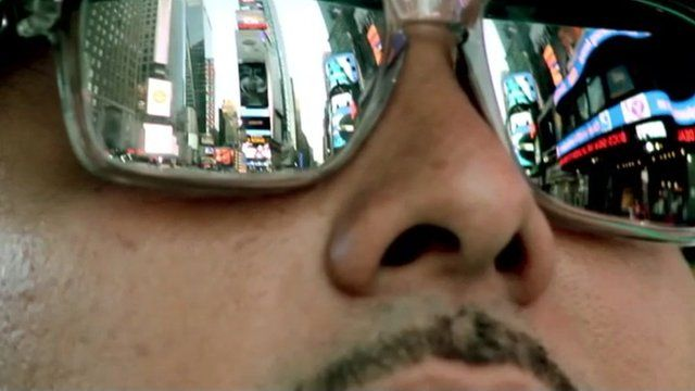 Man with reflection of Times Square in sunglasses