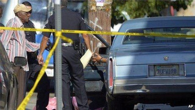 Preston Carter, left, talks to police after the accident outside a South Los Angeles school on 29 August 2012