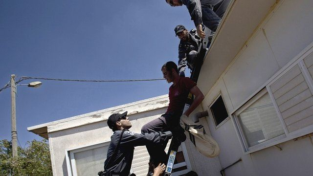 Police remove a settler from a rooftop