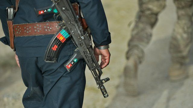 Afghan policeman walking behind US army soldier