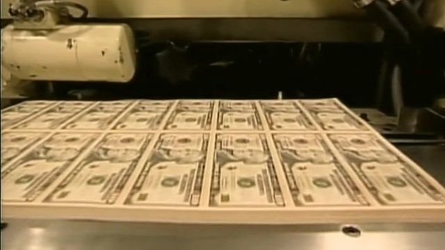 Stack of freshly-printed dollar bills ready to be cut