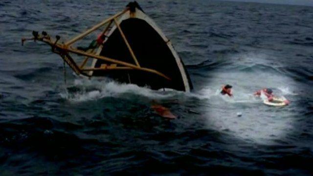 Fishermen in water near sinking trawler