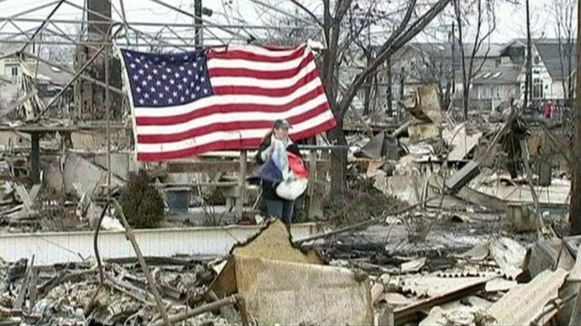Woman stands among rubble after Storm Sandy hit