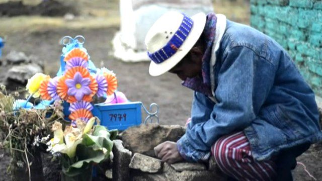 Man kneels by a grave
