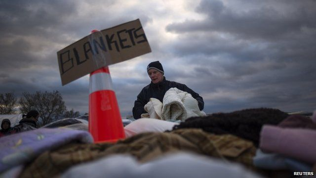 A victim of Storm Sandy takes blankets from a aid distribution site in Staten Island