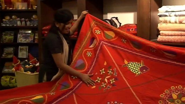 Bangladeshi shop assistant demonstrates a traditional wall hanging