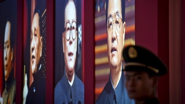 A Chinese paramilitary policeman stands guard next to a display showing four generations of Chinese leaders