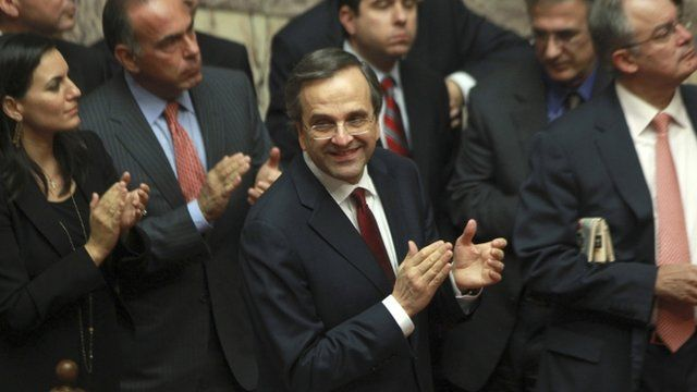 """Greece""""s Prime Minister Antonis Samaras and his party's lawmakers of the New Democracy party applaud after voting on the country's 2013 budget"""