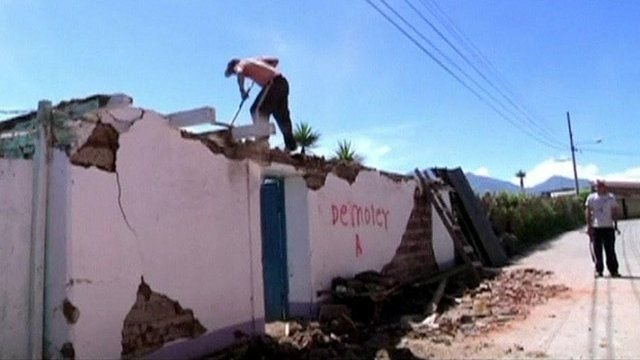 A worker demolishes a house