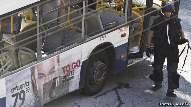 An Israeli police explosives expert walks next to a damaged bus at the scene of an explosion in Tel Aviv